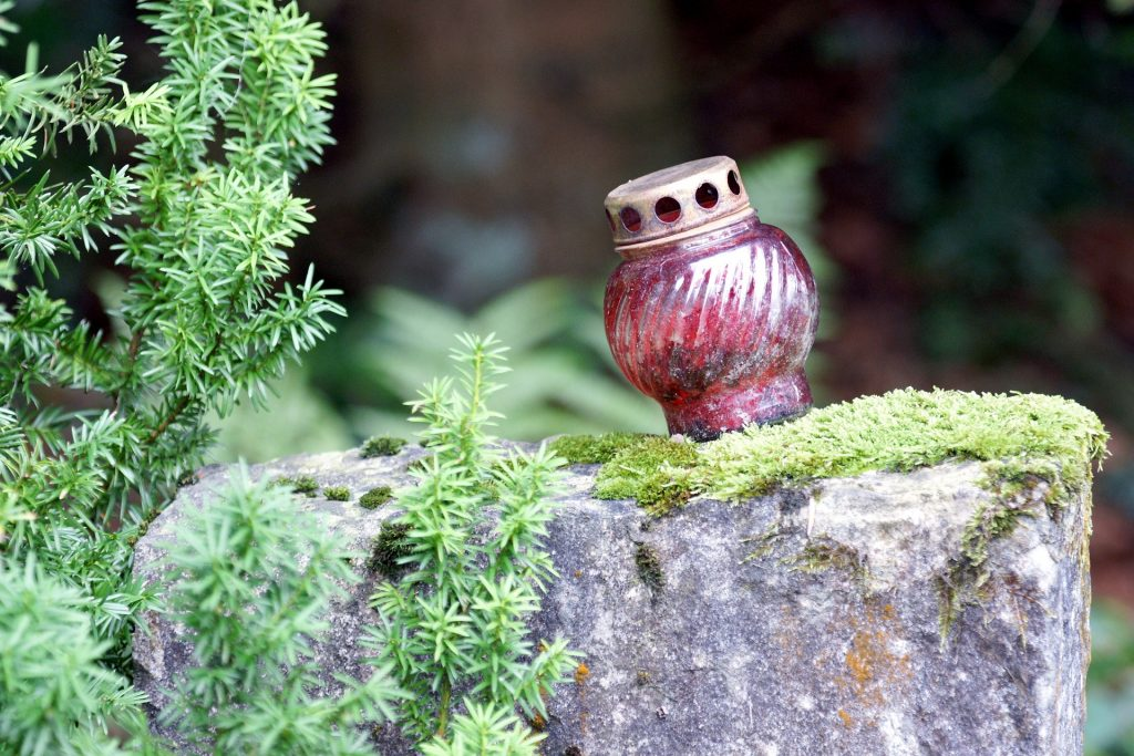 Ein Grablicht steht auf einem mit Moos bewachsenen Stein